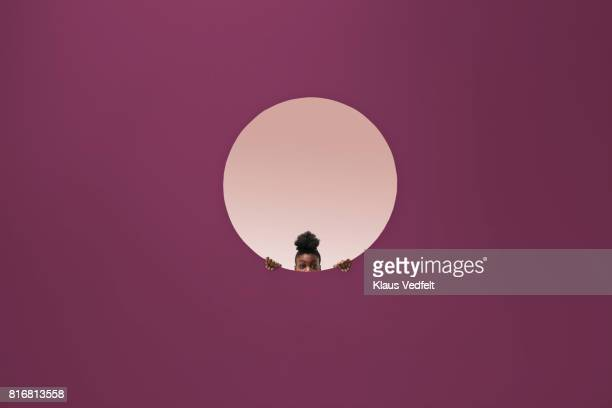 Woman peeking out of round opening in coloured wall