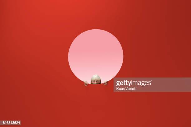 woman peeking out of round opening in coloured wall - caucasian appearance stock pictures, royalty-free photos & images