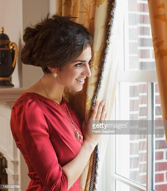 Woman peeking out the window curtain.