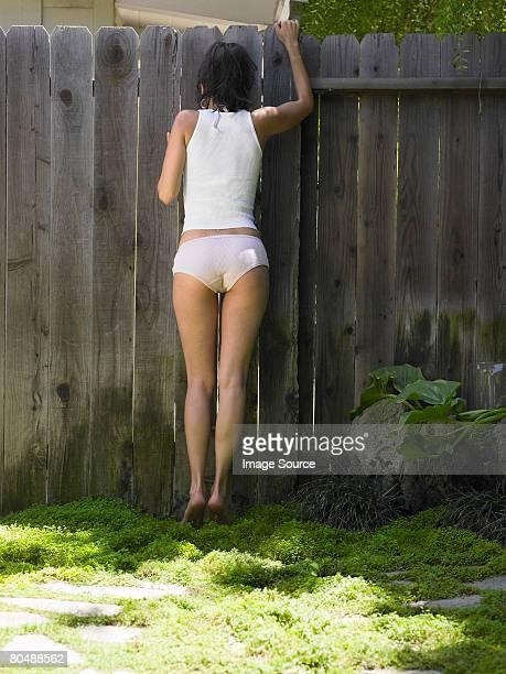 A woman peeking through a fence