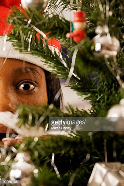 woman peeking through christmas tree branch - african american christmas images stock pictures, royalty-free photos & images