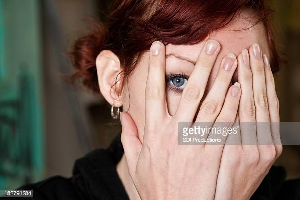 Woman Peeking Through Her Hands