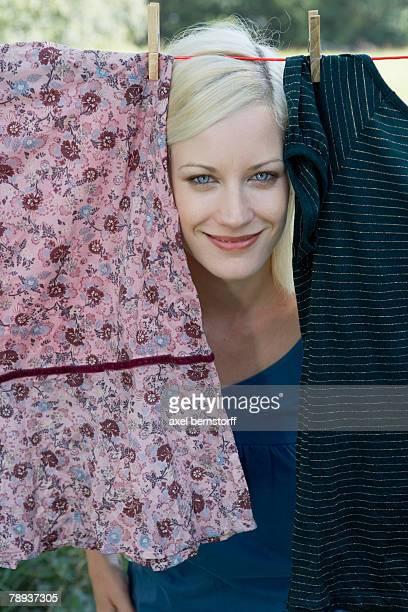 Woman peeking through laundry hanging on clothesline smiling.