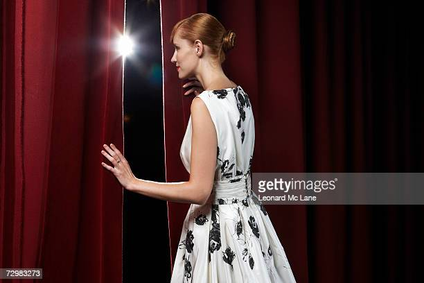 woman peeking through theatre curtains - stage curtain stock pictures, royalty-free photos & images