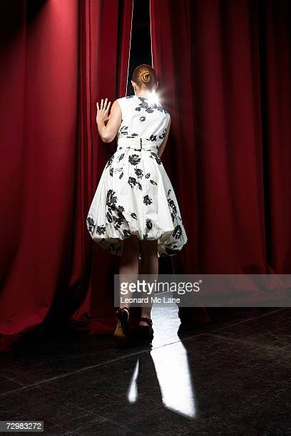 """woman peeking through theatre curtains, rear view"" - stage curtain stock pictures, royalty-free photos & images"