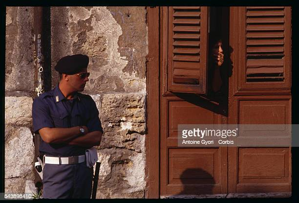 A woman peeks out through a shutter next to a police officer during the funeral of antiMafia judge Paolo Borsellino in Palermo Italy The Mafia...
