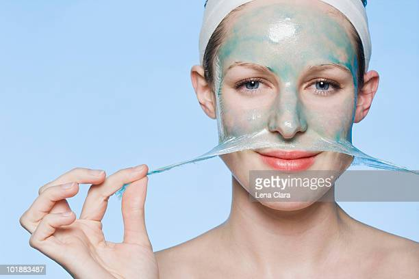 A woman peeling a face mask off her face