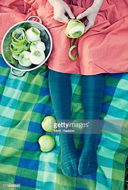 woman peeling apples on vintage blanket - 皮をむく ストックフォトと画像