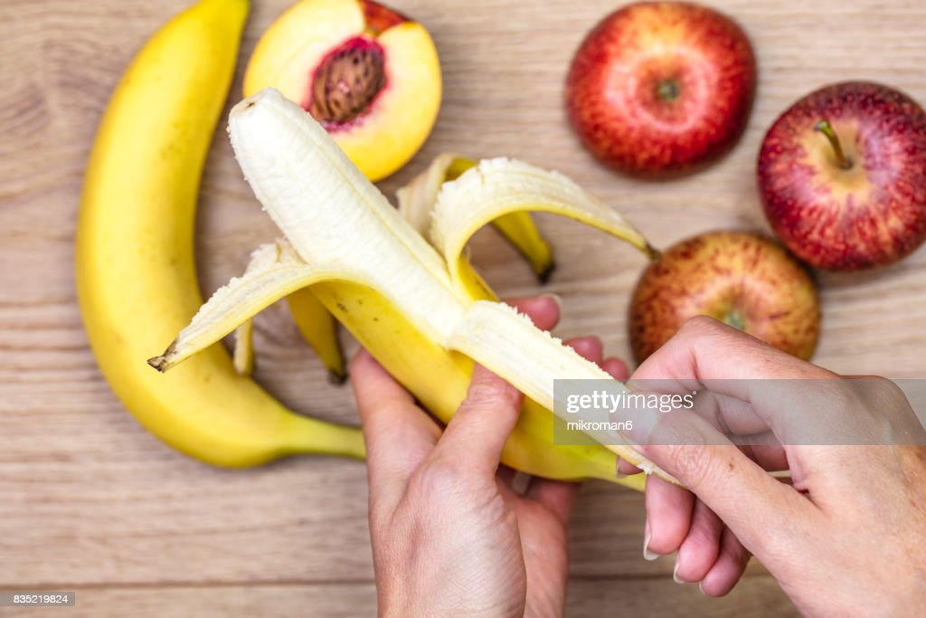 Woman peeling off banana  for healthy eating. : Stock Photo