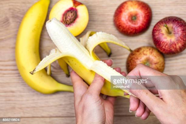Woman peeling off banana  for healthy eating.