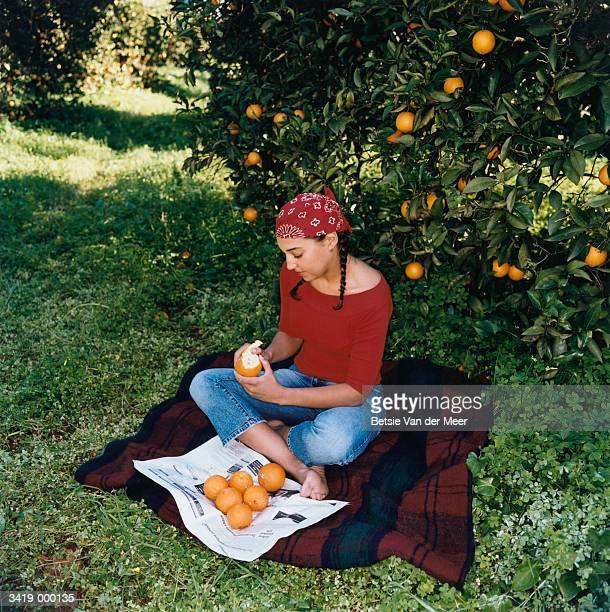 Woman Peeling Orange near Tree