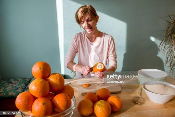 vrouw oranje peeling om sinaasappeljam in binnenlandse keuken - schillen stockfoto's en -beelden