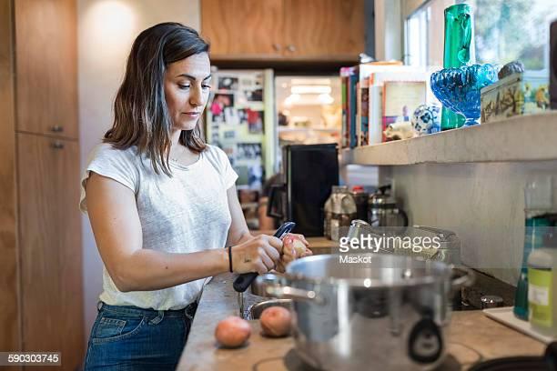 Woman peeling potato at kitchen counter