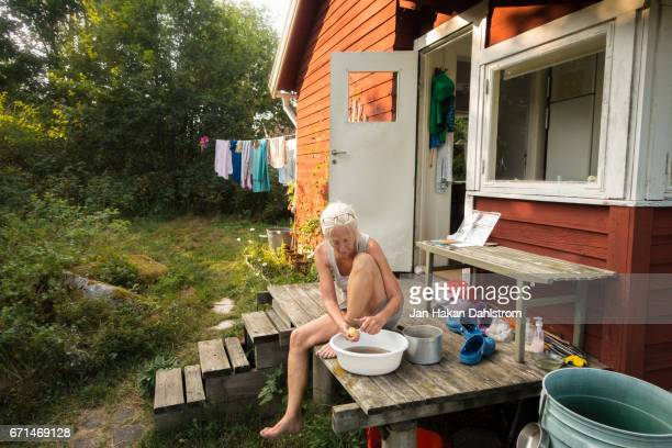 Woman peeling potatoes on cabin porch