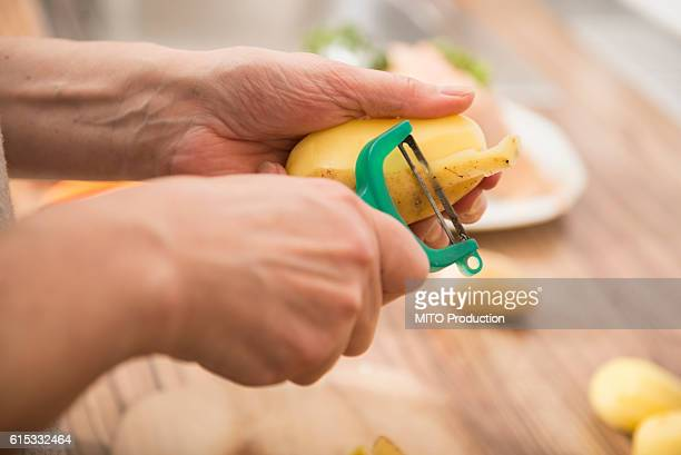 Woman peeling potatoes with a potato peeler in kitchen, Munich, Bavaria, Germany