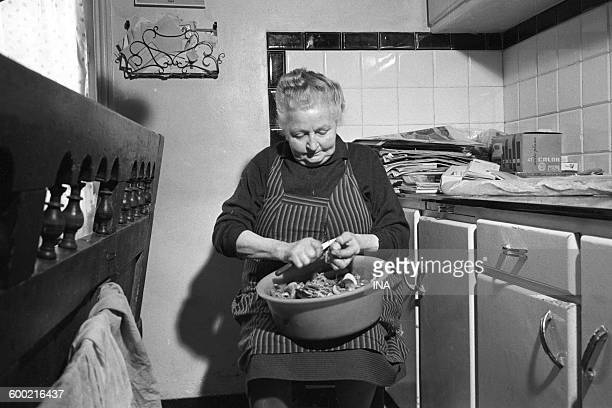 A woman peeling vegetables in a corner of the cooking