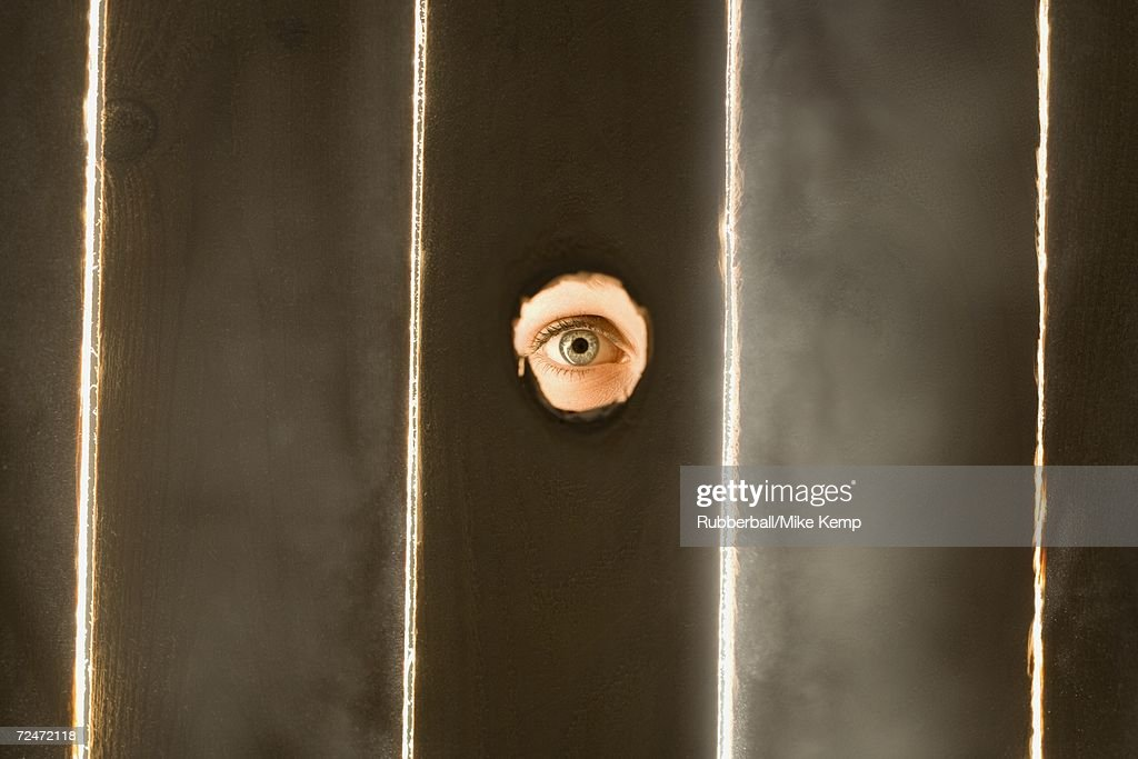 Woman peeping through hole in fence : Stock Photo
