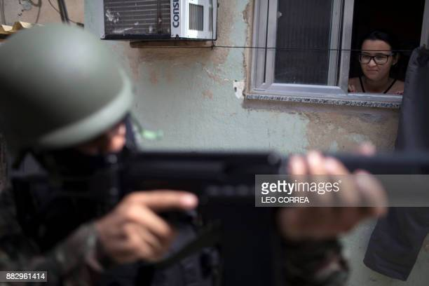 A woman peeps out from a window as an army soldier takes position during a security operation at Barbante favela where earlier in the week alleged...