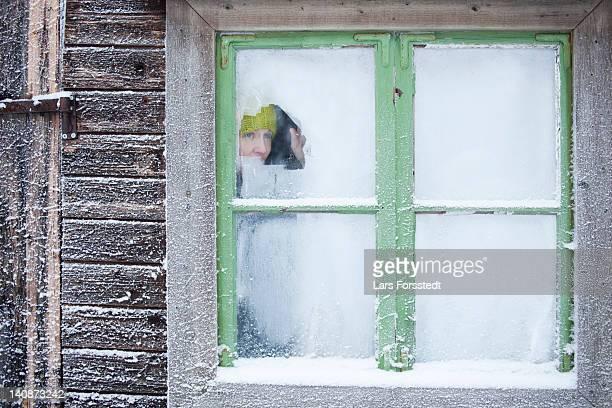Woman peering out frosty window