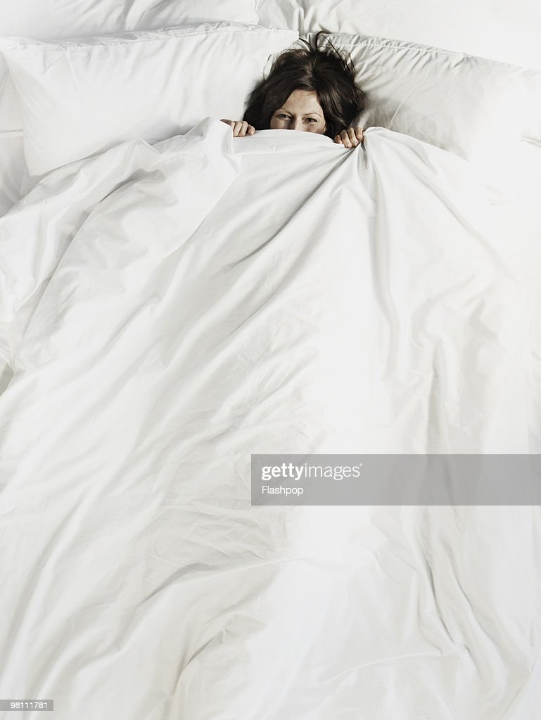 Woman peering over the top of bed sheet : Stock Photo