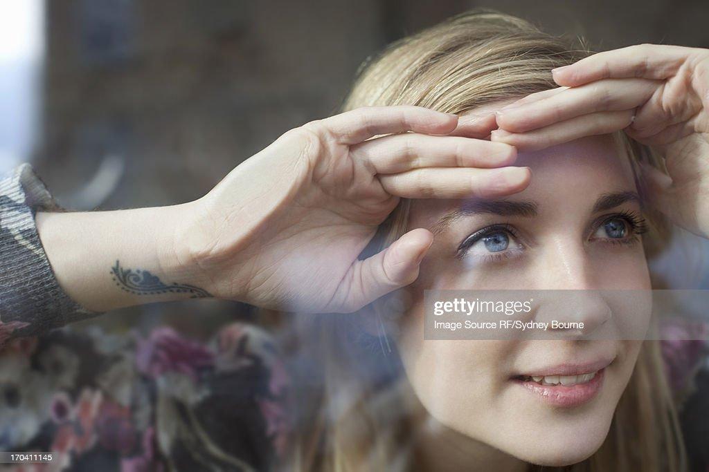 Woman peering through window : Stock Photo
