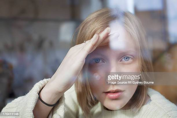 woman peering through window - curiosity stock pictures, royalty-free photos & images
