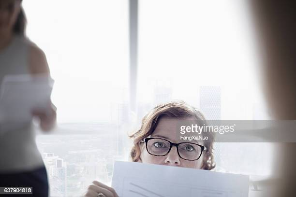Woman peering up from paper document in meeting