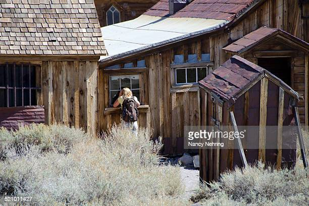 Woman peers inside window of an abandoned house at Bodie State Park California USA The park maintains the Wild West ghost town in a state of arrested...