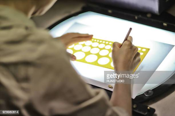 Woman pencil tracing circle template on light table