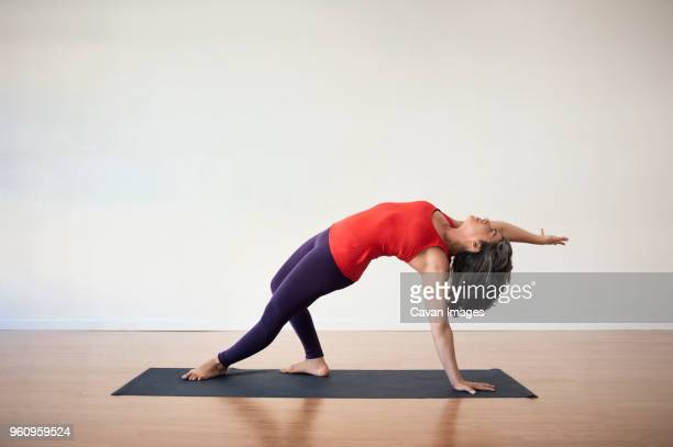 Woman performing balance yoga exercise in health club