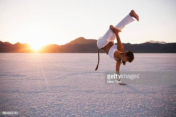 woman performing capoeira on bonneville salt flats at sunset, utah, usa - capoeira imagens e fotografias de stock