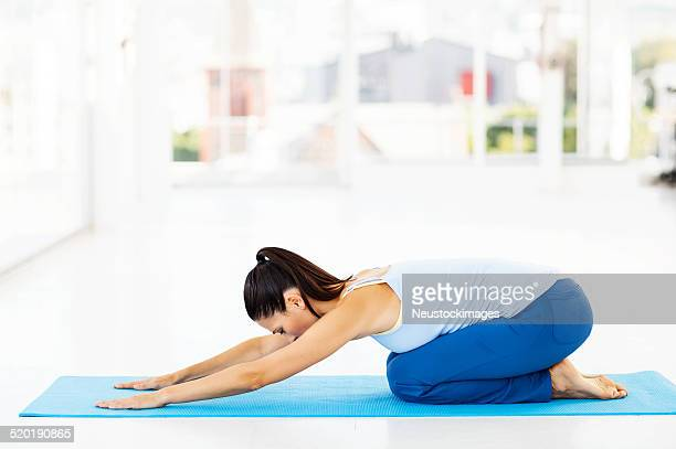 woman performing childs pose in yoga class - childs pose stock photos and pictures
