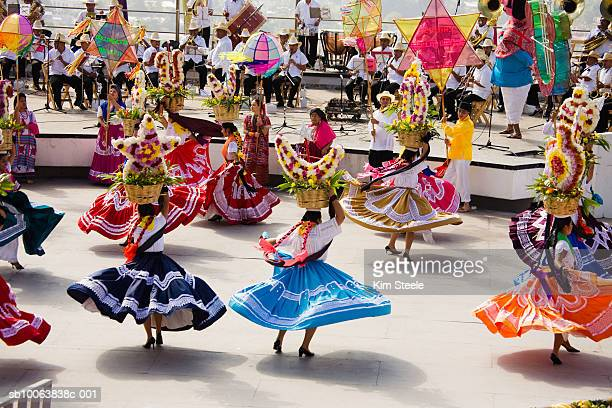 Woman performing Chinas Oaxaquenas dance, musician playing music in background