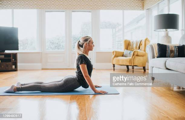 woman performing cobra stretch on a yoga mat - human back stock pictures, royalty-free photos & images