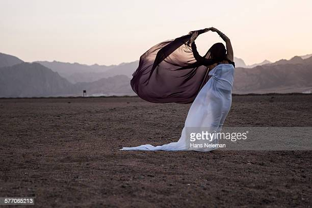 Woman performing dance with hijab-like scarf