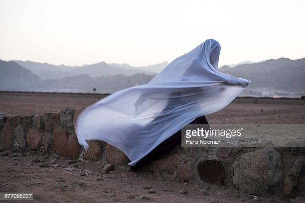 Woman performing dance with hijab-like scarf