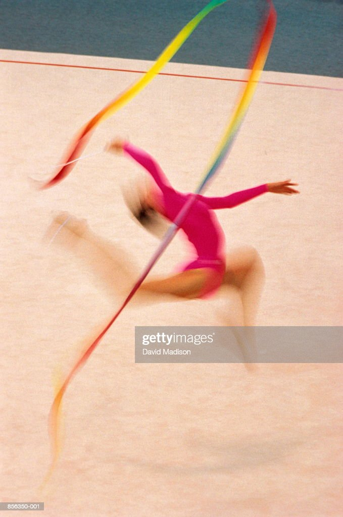 Woman performing  gymnastics routine with ribbons (blurred motion) : Stock Photo