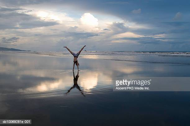 Woman performing handstand on beach at sunset