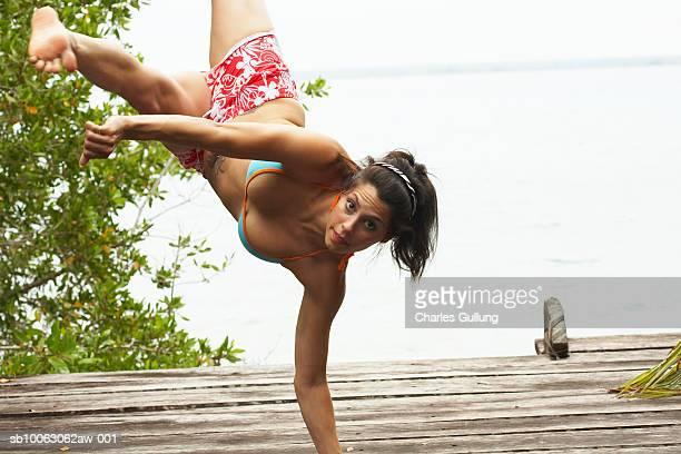 woman performing handstand on jetty, portrait - capoeira imagens e fotografias de stock