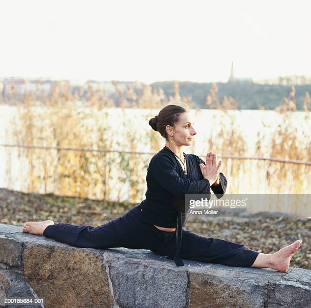 Woman performing 'monkey' yoga position outdoors by water