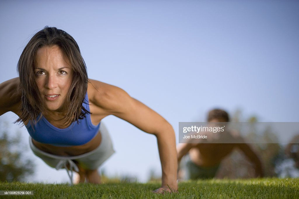 Woman performing push up in park : ストックフォト