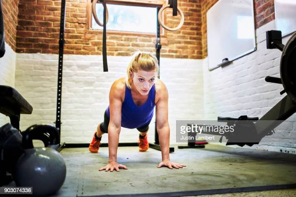 woman performing slow push up in home gym in a converted garage - sports training stock pictures, royalty-free photos & images