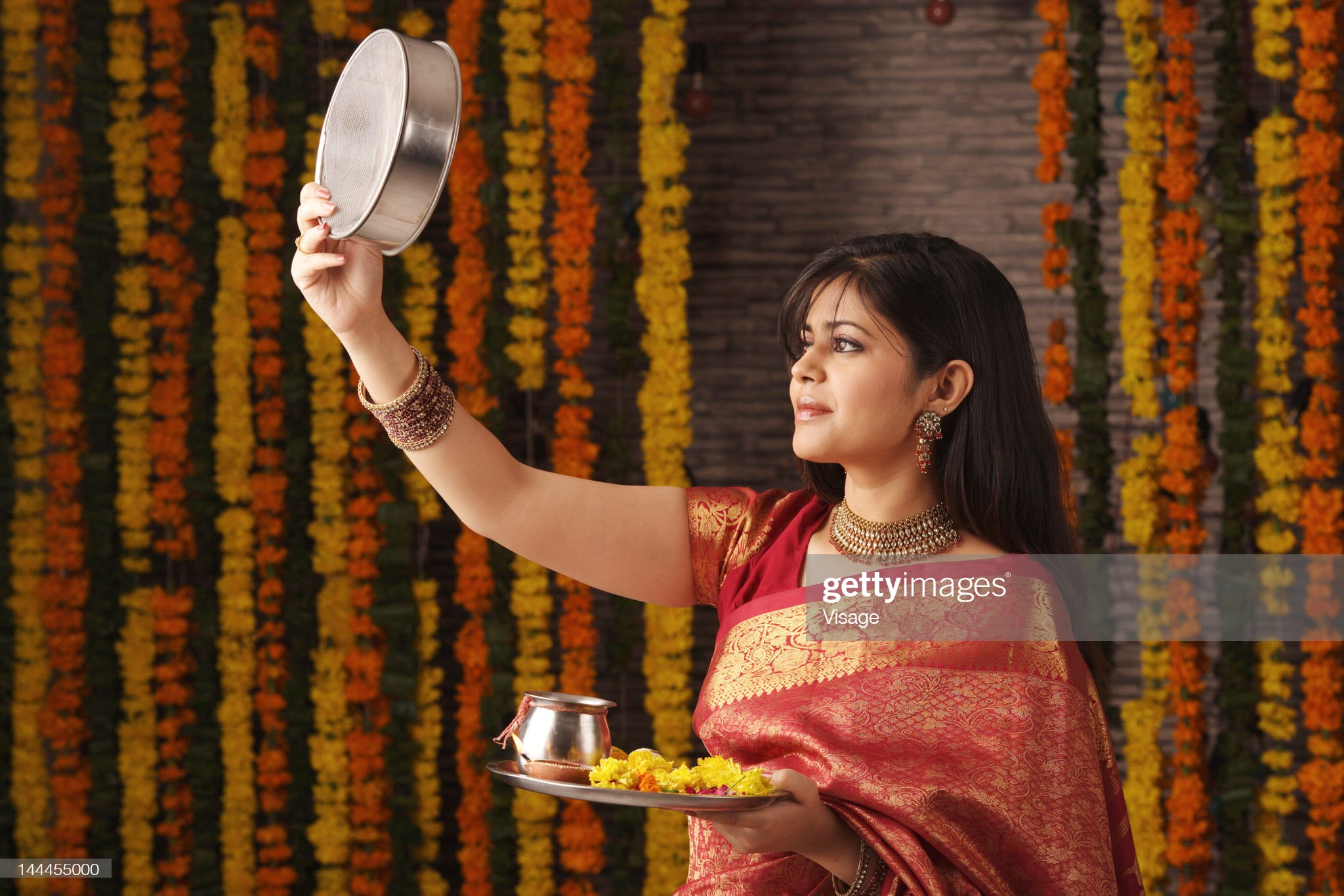 A woman performing the Karva chauth ritual : Stock Photo