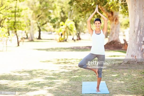 Woman Performing Yoga In Tree Pose At Park