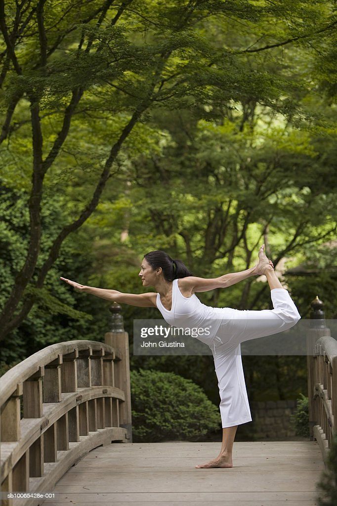Woman performing yoga on bridge in Japanese garden : Foto stock