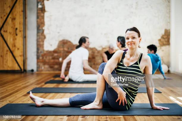 woman performing yoga poses - personne secondaire photos et images de collection