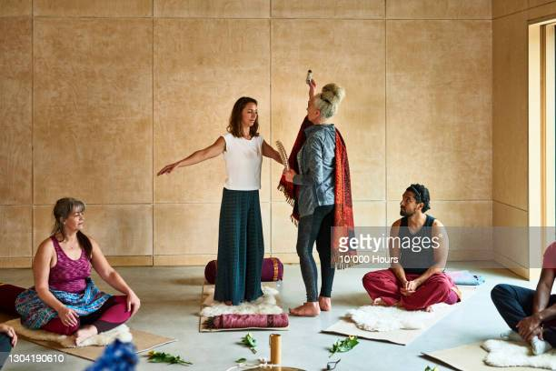 woman performing yoga ritual using smudge stick and feather - participant stock pictures, royalty-free photos & images