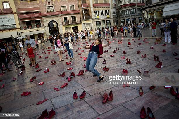 A woman performs flamenco dance among 745 pairs of red shoes at the Constitucion square in Malaga where the Mexican artist Elina Chauvet's...