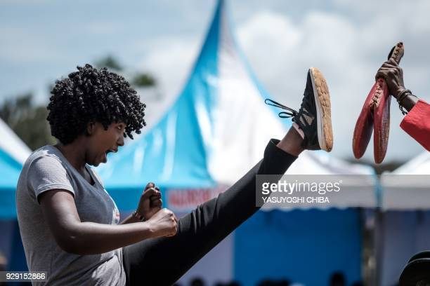 TOPSHOT A woman performs taekwondo during the ceremony of the International Women's day at Kawangware in Nairobi on March 8 2018 / AFP PHOTO /...