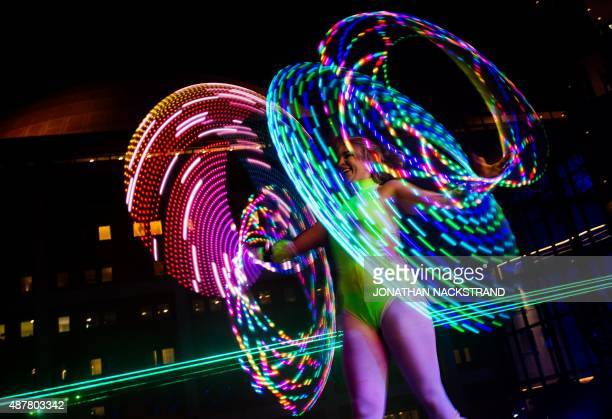 A woman performs with a hula hoop during the 'The Color Run Night' in Stockholm on September 11 2015 The Color Run founder Travis Snyder was inspired...